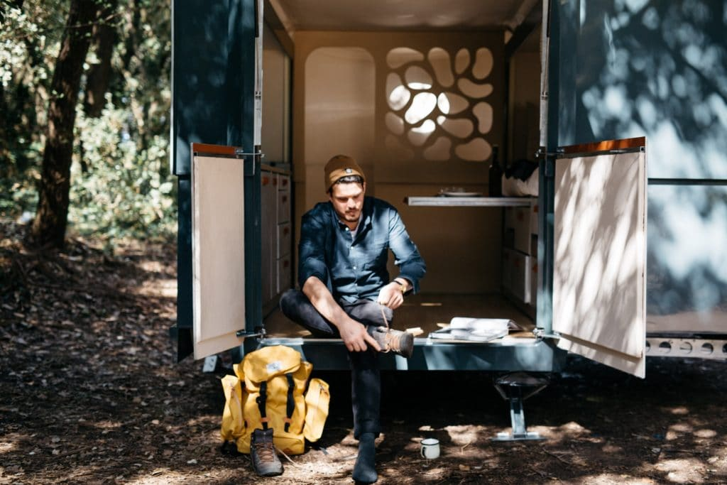 Man Sitting on tall Enclosed trailer tying shoes